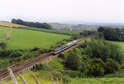 A pairing of 150249 and 158869 are about to  pass the site of Wishing Well Halt on the climb away from Weymouth with 2V83 1500 off to Bristol.  27/7/2002