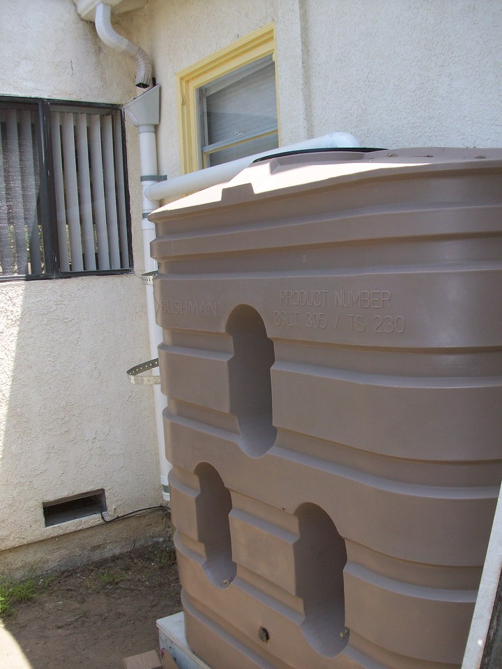 "305 gallon tank installed in Santa Monica. Unfortunately the pipe had to visibly cross a window, but as this spot on the property collected the most roof area, it was the best place for it and the one selected by the homeowner. <a href=""http://www.rain-watersystems.com/"">http://www.rain-watersystems.com/</a>"