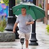 BEN GARVER — THE BERKSHIRE EAGLE<br /> Joe Gennari crosses the street downtown. With rain forecast for the entire day, there is no escaping the rain in Pittsfield.