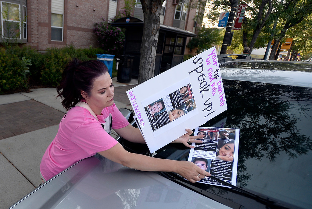 . Jacki Montoya puts a flyer on a car windshield while trying to raise awareness for the disappearance of Rita Gutierrez-Garcia on Friday on Main Street in Longmont. For more photos go to dailycamera.com Jeremy Papasso/ Staff Photographer 08/03/2018