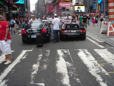 Peter and Bart conspiring between the Bentley and the Lotus in Times Square.