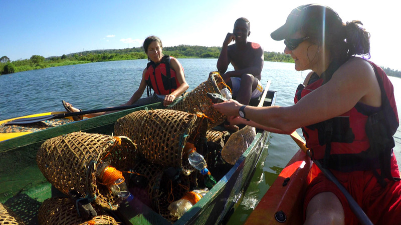 Tiffany checks out Grezzo's fishing baskets that he weaved himself to catch the bait for the bigger fish on the Nile in Uganda.