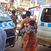 Ugandan baby wrapped tightly against her mother as they weave in and out of the crazy traffic of Kampala, Uganda.