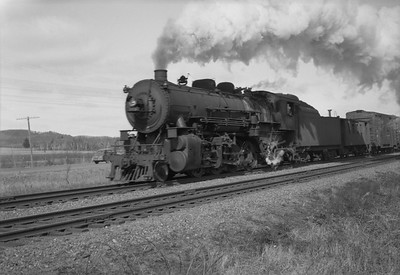 2021.001.NO.04.007--ralph wehlitz 6x9 neg [photographer unknown]--CStPM&O--steam locomotive 2-8-2 J-A 399 with caboose and freight cars action--Merrillan WI--no date