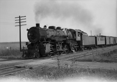 2021.001.NO.04.009--ralph wehlitz 6x9 neg [photographer unknown]--CStPM&O--steam locomotive 2-8-2 J-A 404 with caboose and freight cars action--near Merrillan WI--no date