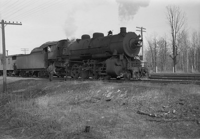 2021.001.NO.04.008A--ralph wehlitz 6x9 neg [photographer unknown]--CStPM&O--steam locomotive 2-8-2 J-A 399 with caboose and freight cars--Merrillan WI--no date