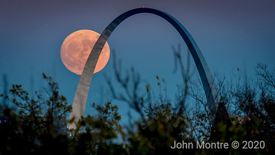 "The ""supermoon"" rises alongside the Jefferson Memorial Gateway Arch in St. Louis."