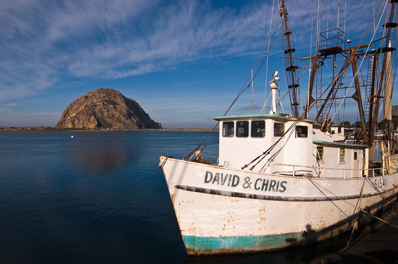 """Day #18 - Not so Deadly Catch<br /> <br /> This is a working fishing boat docked at the wharf in Morro Bay, CA.  The rock in the background is Morro Rock, where the town get's it's name.  She is one of the """"Nine Sisters of San Luis Obispo"""", a series of rock formations that are located along this part of the Central California Coast. <br /> <br /> I took this shot in morning light using my newest lens, a Tokina 11-16mm Wide Angle.  I had the aperture set at f/16 to get a nice DOF.  I really love this lens and I am glad I waited out the backorder of 6 months to get instead of comprimising on a different lens."""