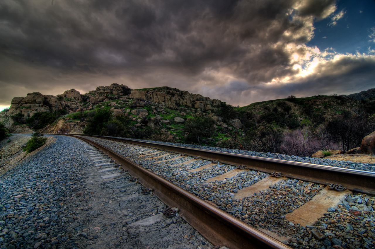 Day #47 - Sunny Days To Come<br /> <br /> Tired of the railroad tracks yet?  This is the last in the series of R&R HDR shots.  Not sure how I feel about this one.  I like how the sky is beginning to clear in the top right and the sun breaking through the clouds.  I also like how tracks curve right out of the image.  Not sure about the angle of the tracks in the foreground.  My cameras was level when I shot this but I don't remember the tracks having such a steep bank when I was there.  Maybe lens distortion since I was shooting with an ultra-wide angle.