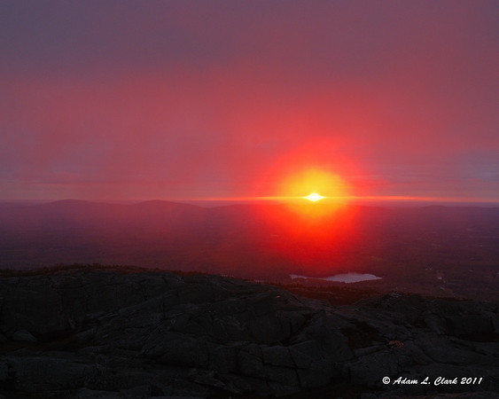 """10.22.2011  Hike #20 of the year up Mt. Monadnock today.  I got up early and hiked up in the dark for the sunrise.  Even being mostly cloudy it was still nice as the sun rose through the one open spot to the East and the thin clouds passing the summit caught even more of the light  For the rest of the gallery, click <a href=""""http://sdways01.smugmug.com/Mt-Monadnock/2011/Sunrise-10-22-2011-Climb/"""">here</a>"""