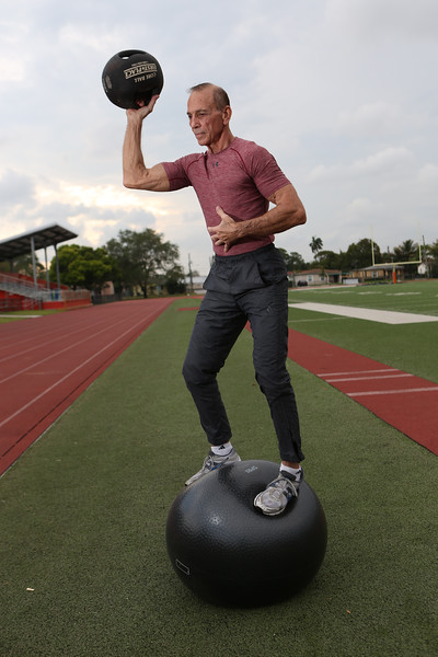 Photo / Candace West, for the South Florida Sun Sentinel.<br /> April 2, 2017,<br /> Ted Kalaidi, is a 73-year-old retired police lieutenant from Jupiter who competes in track and field. Kalaidi lifts a 14 pound medicine ball while balancing on a SPRI ball for his core strength.