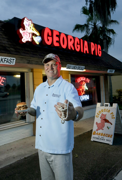 Georgia Pig BBQ & Restaurant<br /> 1285 S State Road 7 <br /> Fort Lauderdale, Florida 33317 <br /> Eric Barton story on Luke Moorman. His family owns Carroll's Jeweler's and the Georgia Pig. The story is t how he juggles those two very different lives, changing from his Carroll's shirt to his camo Georgia Pig hat when he drives between the two.<br /> Photo / CandaceWest.com, for the South Florida Sun Sentinel.