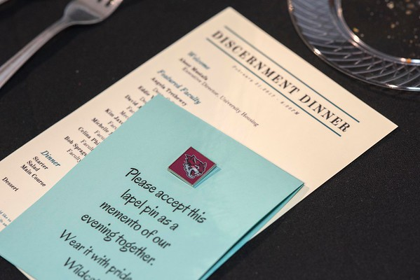 A pin for student residents that enjoy a formal dinner and hear professors talk about their experiences during the Discernment Dinner in the Whitney Study Lounge on Tuesday, February 21, 2017 in Chico, Calif.  (Jason Halley/University Photographer)