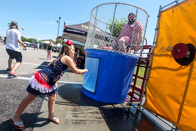 McKala Sallie hits her target at the dunk tank as Cape Beard: Follicles of Freedom holds their 6th annual Pig Pickin' benefiting the Autism Society of Cumberland County at Fort Bragg Harley Davidson on Saturday, May 27, 2017. [Raul F. Rubiera/The Fayetteville Observer]