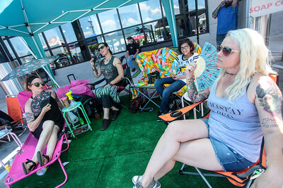 Patrons relax in the shade as Cape Beard: Follicles of Freedom holds their 6th annual Pig Pickin' benefiting the Autism Society of Cumberland County at Fort Bragg Harley Davidson on Saturday, May 27, 2017. [Raul F. Rubiera/The Fayetteville Observer]