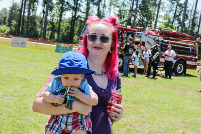 Lauren Martin and baby Sully explore the fire truck as Cape Beard: Follicles of Freedom holds their 6th annual Pig Pickin' benefiting the Autism Society of Cumberland County at Fort Bragg Harley Davidson on Friday, May 27, 2017. [Raul F. Rubiera/The Fayetteville Observer]