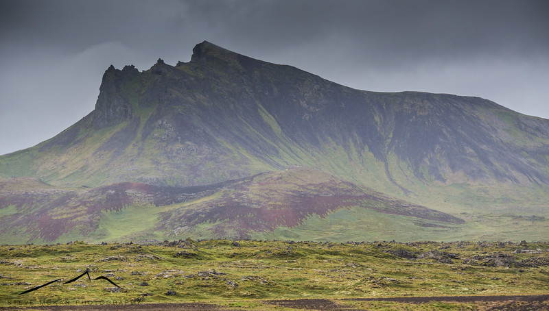 """You can see where this peak """"blew open"""" and spewed lava into the open space below.  These types of mountains are everywhere in Iceland."""