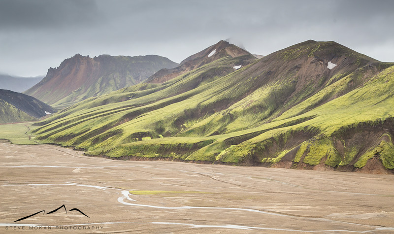 Small, flat river drainages lead up to perfectly carved mountains.