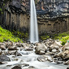 A picture perfect waterfall against eroded basalt columns.