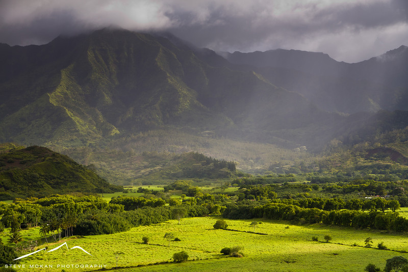 A storm passes behind Hanalei while the sun peeks through in the foreground.  Look closely and you can see the rain showers moving out on the right side.