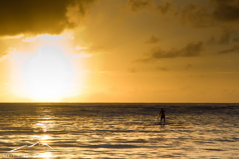 A stand-up paddleboarder enjoys Hanalei Bay at sunset.