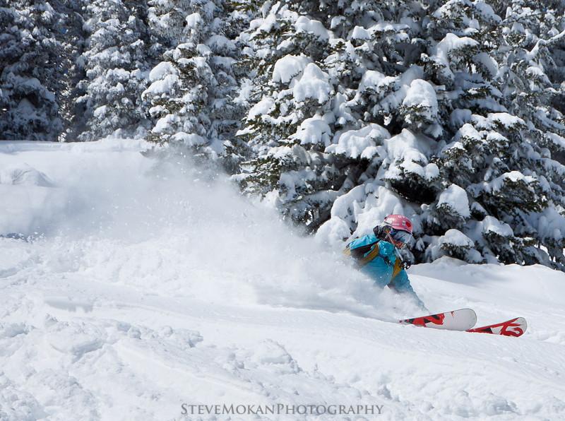 Still smiling, Kim enjoys the bottomless pow on her gigantic powder skis.