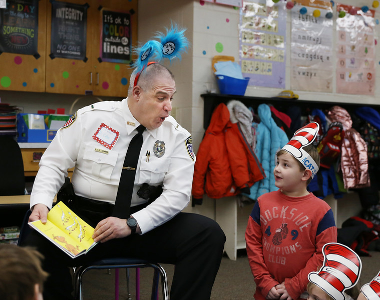 HOLLY PELCZYNSKI - BENNINGTON BANNER Channing Stephens. looks over at  lieutenant Cam Grande as he reads to the first grade class of Mrs. Saddlemire at Molly Stark School in Bennington on Monday morning during the Dr. Seuss's birthday and Read Across America event.