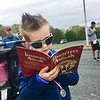 Casey Wayne, 5, of Billerica, read the free book he received after finishing the Dewey Dash. Photo by Mary Leach