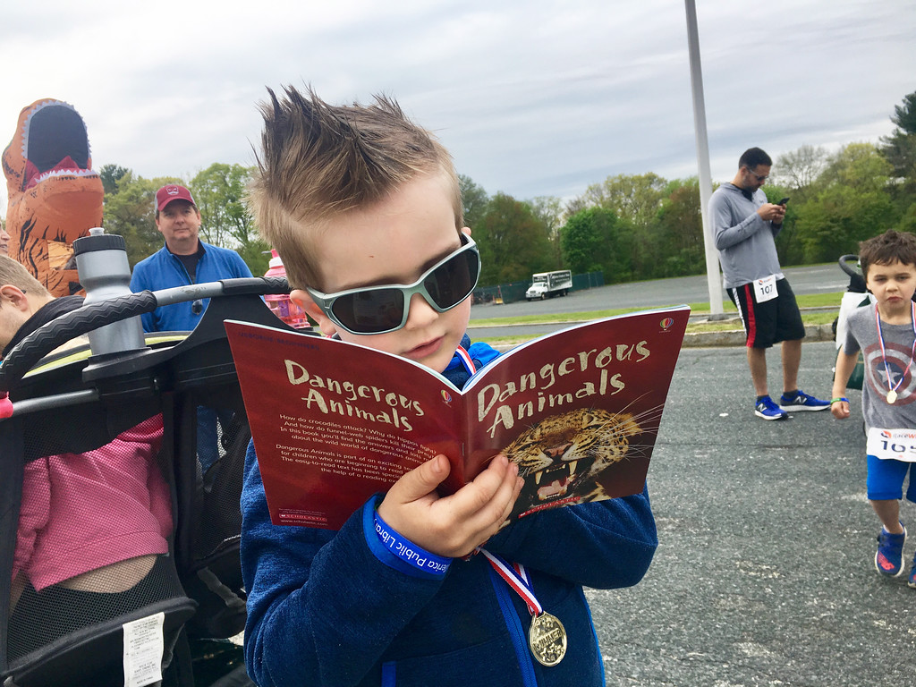 . Casey Wayne, 5, of Billerica, read the free book he received after finishing the Dewey Dash. Photo by Mary Leach