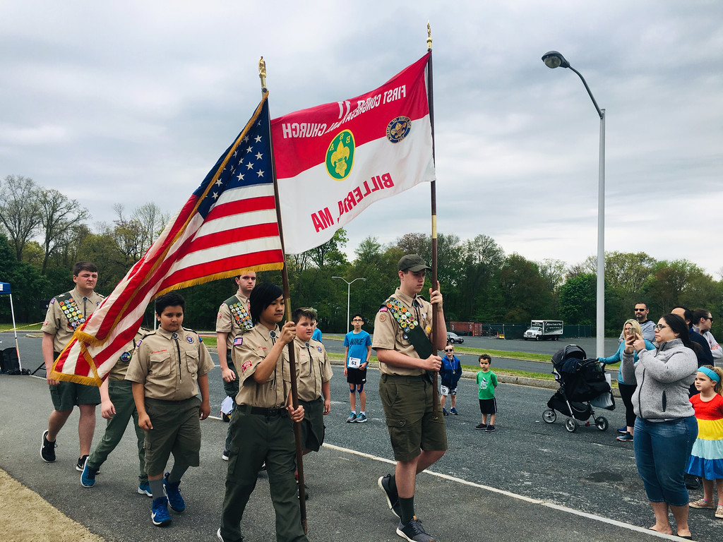 . Scouts from Billerica Troop 11 presented the colors before the road race. Bruce the Turtle (Ava Gottman-Hanrahan) helped Sydney Petcher of Billerica warm up before the Dewey Dash. Photo by Mary Leach