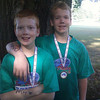 Brothers Gradyn and Brendyn Rogers wearing their participation awards for the 2012 Kokomo Sports Center Tryathlon.  They are cooling off under one of the Kokomo Country Club trees.<br /> <br /> Photographer's Name: Randy Rogers<br /> Photographer's City and State: Kokomo, IN