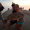 Chesney Kerr, age 9, caught this monster fish with her daddy Zach Kerr while on vacation in Holland, Michigan. Proud Papaw Smith had to get a picture taken with her and the fish:)<br /> <br /> Photographer's Name: Brandy Kerr<br /> Photographer's City and State: Anderson, Ind.