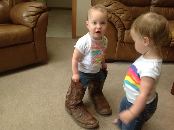 Sophie Bell in her Grandpa Watson's old cowboy boots with twin sister McKenzie admiring them.<br /> <br /> Photographer's Name: Carole Bell<br /> Photographer's City and State: Anderson, Ind.