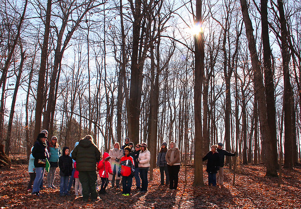 Kelley Morgan from Mounds Park leading a Winter Solstice hike with a sun burst showing.<br /> <br /> Photographer's Name: Jerry Byard<br /> Photographer's City and State: Anderson, Ind.