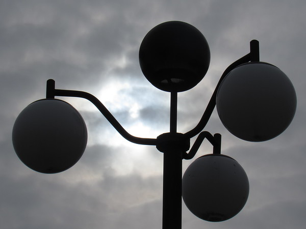 Sun, peeking out of the clouds, among the lighting bulbs.<br /> <br /> Photographer's Name: Harry Van Noy<br /> Photographer's City and State: Lafayette Township, Ind.