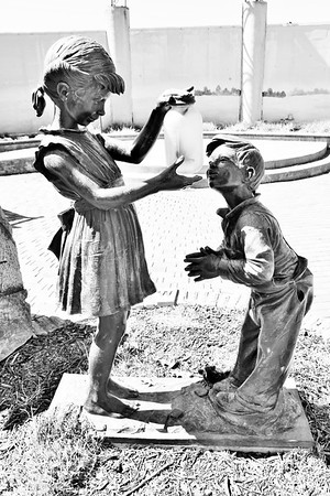 Girl and boy statues looking at fireflies in Muncie.<br /> <br /> Photographer's Name: Rebecca Reding<br /> Photographer's City and State: Anderson, Ind.