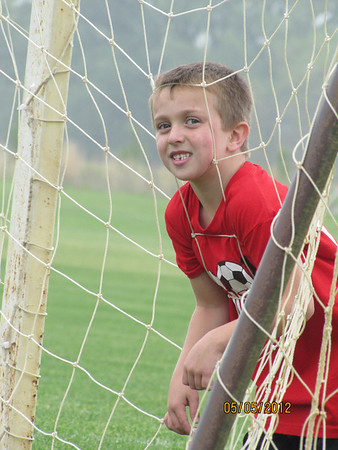 Jackson watching his sister's game through the net after his game at Davis Park for the YMCA.<br /> <br /> Photographer's Name: JoAnna Mullins<br /> Photographer's City and State: Anderson, IN