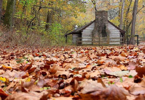 A leaf-covered ground and cabin in the village at Spring Mill State Park.<br /> <br /> Photographer's Name: Jerry Byard<br /> Photographer's City and State: Anderson, Ind.