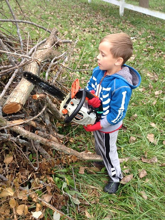 """Why mothers get gray...Eli Coxe """"pretending"""" to work a chainsaw.<br /> <br /> Photographer's Name: J.R. Rosencrans<br /> Photographer's City and State: Alexandria, Ind."""