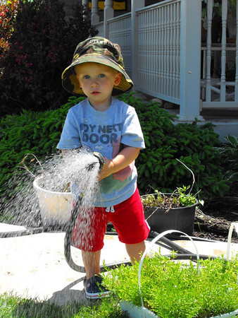 """Yard work:"" grandson Eli Coxe watering the yard.<br /> <br /> Photographer's Name: J.R. Rosencrans<br /> Photographer's City and State: Alexandria, Ind."