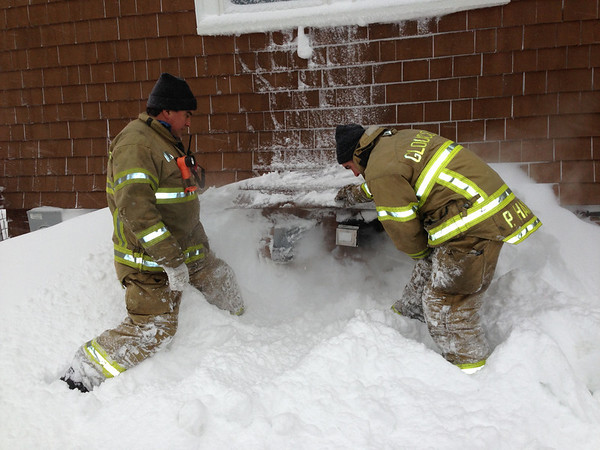 Firefighter Bud Doucette and Capt. Phil Harvey clear snow from a home's furnace vents after the carbon monoxide detector alarm triggered. Please make sure your home's vents are clear! <br /> <br /> Photographer's Name: Michael  Chipperini<br /> Photographer's City and State: Gloucester, MA