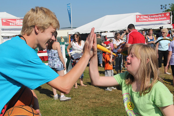 """<span style=""""display:none"""">Email: kimberlynewslady@yahoo.com</span> <b>Submitted By:</b> Kimberly Purdy <b>From:</b> Traverse City <b>Description:</b> A volunteer high fives a special kid on Special Kids Day in the Open Space."""