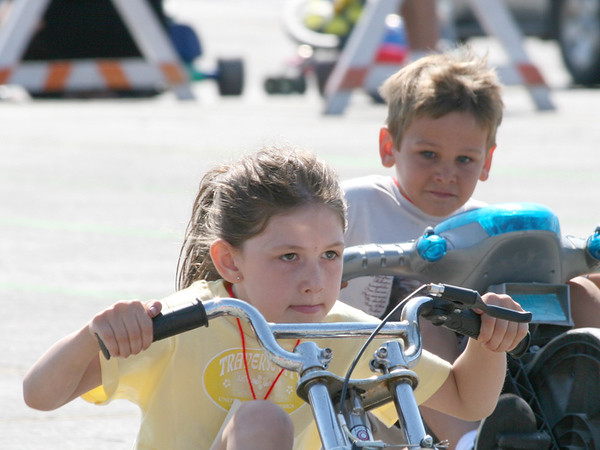 Taken at the Big Wheel Race 2008<br /> This young lady won this heat. I love the look on the boy's face as he <br /> realizes that he's being beat by a girl.<br /> <br /> David Bajema<br /> Long Lake Township