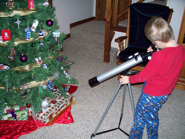 "The story behind this photo is quite humorous.  I was wrapping presents last <br /> night and my son woke up and noticed them right away.  I told him he could <br /> guess what was inside as much as he wanted, but he was not allowed to touch <br /> them.  The next thing I knew, he was carrying his brother's telescope <br /> downstairs and set it up in front of the tree.  This was his way of getting <br /> a ""closer look"" at the gifts!<br /> <br /> I thought readers might get a good laugh at his creativity.<br /> <br /> Merry Christmas!<br /> Rachel Stivani, Traverse City."