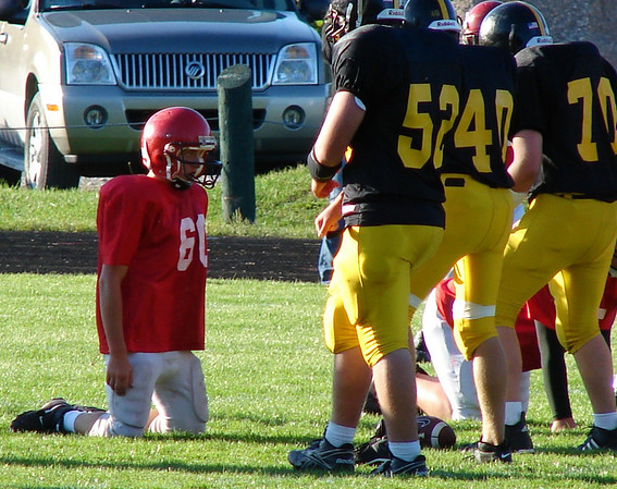 """My goodness, they grow 'em BIG in Glen Lake.""<br /> <br /> Suttons Bay middle school, Kaleb Schaub against the Glen Lake linebackers.<br /> <br /> Photo taken at Glen Lake field, mid September 2008 by Sheila Schaub from <br /> Suttons Bay."