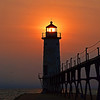 <b>Submitted By:</b> Steve Nowakowski <b>From:</b> Lambertville, MI. <b>Description:</b> Sunset through Manistee Pier light in the summer of 2011.