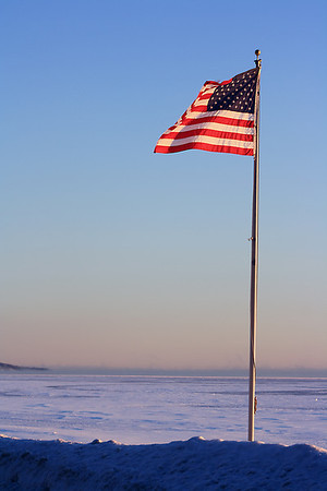 In Michigan Inauguration Day dawned bright and clear.  It was a day I could <br /> not resist getting out with my camera dispite the cold.  As I drove along <br /> East Bay, I found this wonderful Flag brillantly lit with sunshine.  Could <br /> it be a sign of good things to come?<br />  Taken by Peggy Sue Zinn