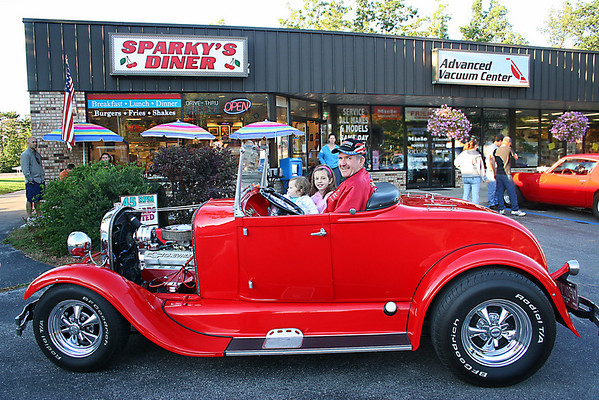 I just happen to catch this wonderful shot of Louie LaFranier out for a <br /> cruse with his Granddaughters in his 1929 Ford with a 355 Chevy engine,  He <br /> had Joined the TC Classic Car Club out for an evening get together at <br /> Sparky's Dinner.  It was so neat to see so many old cars so lovingly <br /> restored, a real blast from the past!   Photography by Peggy Zinn