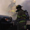 Firemen putting out Car Fire at 42nd street shopping Plaza by Peggy Zinn <br /> owner of Candid Lens Studios, Taverse city Michigan.
