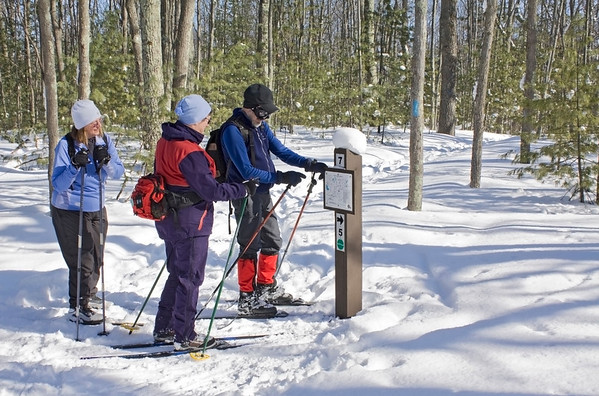 This is a picture of 3 people looking at something.  In this case, it's a <br /> trail map at the Muncie Lakes Pathway Cross Country Ski Trail, during the <br /> best snow year ever!  The people are Pam, Lois and Harold.  It was taken <br /> Feb. 23, 2009.<br /> <br /> Taken by John Heiam, Williamsburg MI